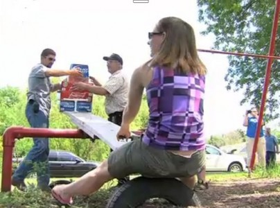 wife carrying winner weighing beer on teeter totter