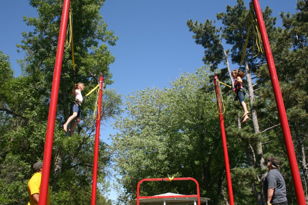 Sofia Losure, left, and Maddie Sumption, right, enjoy the bungie trampoline during Finn Fest in Frederick, June 15, 2013.