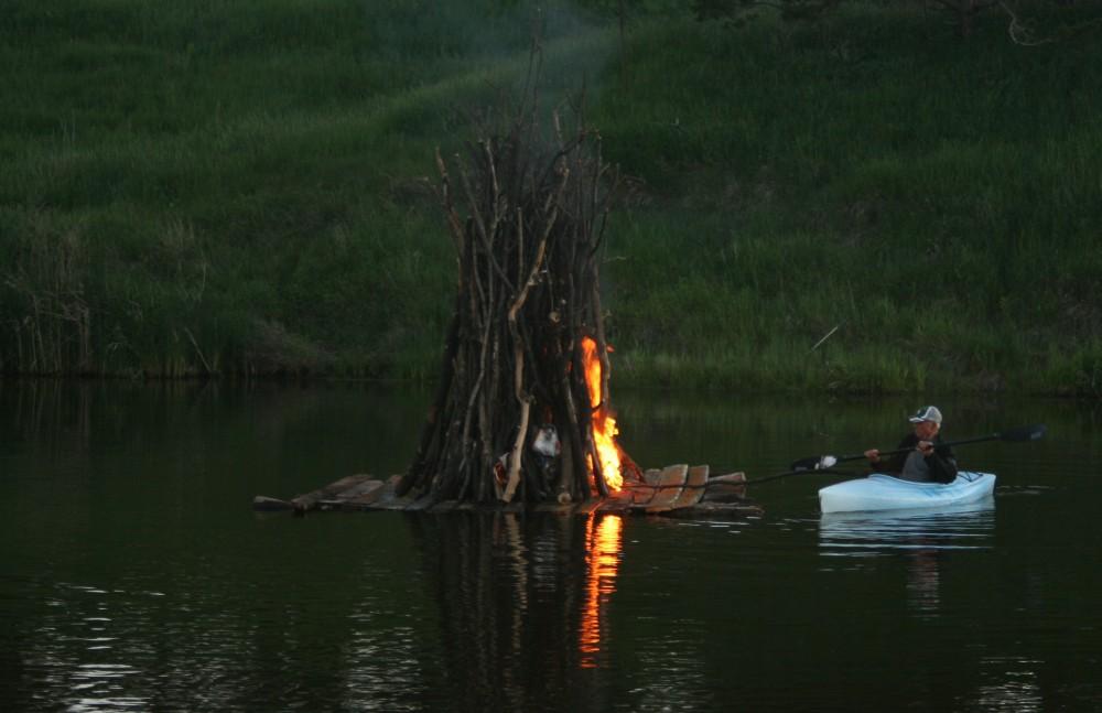 Dale Groop lights the juhannuskokko, or midsummer bonfire, on the Maple River in Frederick, S.D., during Finn Fest on June 15, 2013.