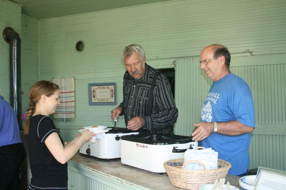 Jim Dumire, center, and Calvin Raisanen serve mojakka (stew) to Marianne Marttila-Klipfel at Savo Hall during Finn Fest 2013.