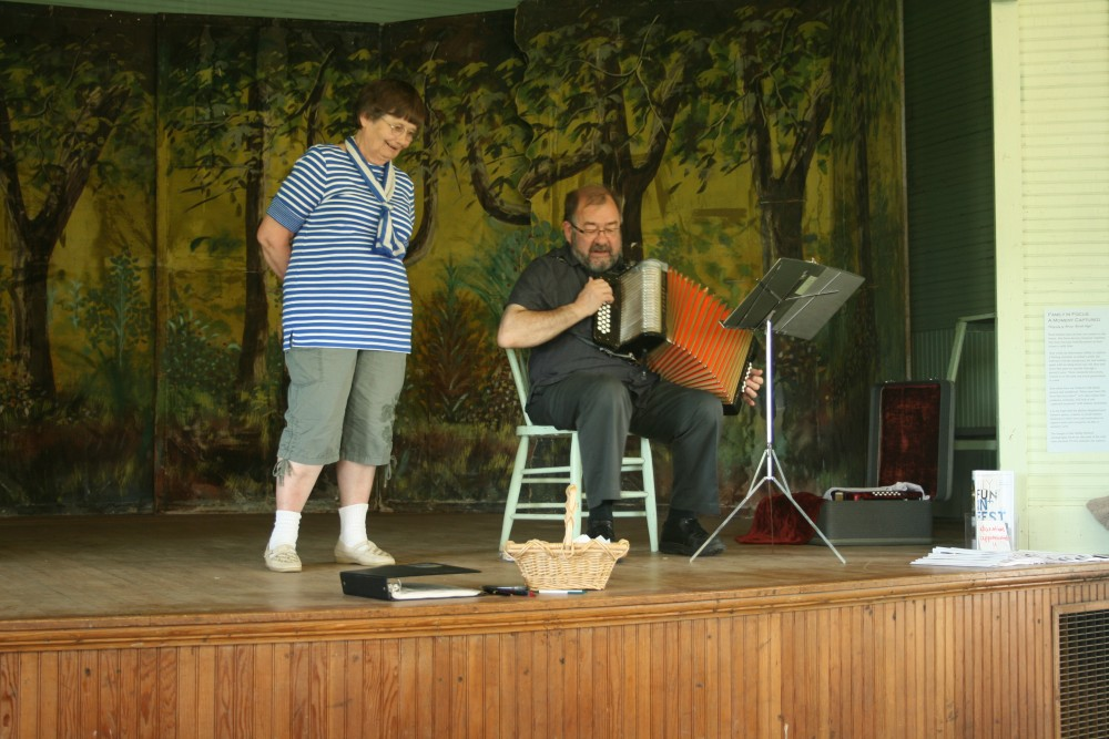 """Annikki Marttila of Frederick, S.D., joins Larry """"Lauri"""" Saukko of Bemidji, Minn., in singing a Finnish song during a presentation of traditional music by Saukko at Savo Hall in rural Frederick, S.D., during Finn Fest."""